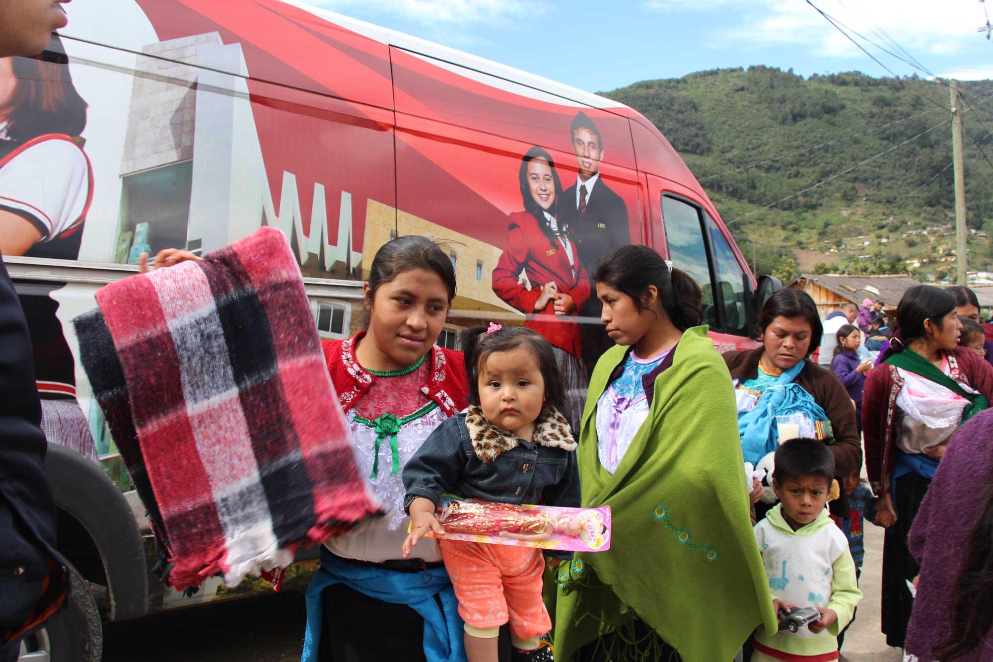 Niños, niñas y adultos recibiendo ropa, refrigerios y juguetes